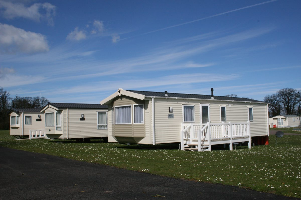 holiday home on a communal park and a clear blue sky in the background, holiday home, Holiday Home Buying Guide, holiday home in kent, holiday home parks in kent